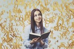 Muchacha adolescente alegre con un libro, letras del oro Imagen de archivo libre de regalías