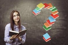 Muchacha adolescente alegre con un libro, pregunta, libros Foto de archivo