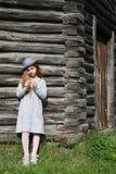 Muchacha adolescente alegre en ropa casual y el sombrero azul que presentan por una madera Fotografía de archivo libre de regalías
