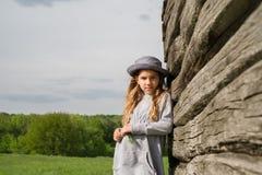 Muchacha adolescente alegre en ropa casual y el sombrero azul que presentan por una madera Imagenes de archivo