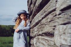 Muchacha adolescente alegre en ropa casual y el sombrero azul que presentan por una madera Foto de archivo