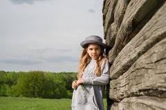 Muchacha adolescente alegre en ropa casual y el sombrero azul que presentan por una madera Fotos de archivo