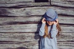 Muchacha adolescente alegre en ropa casual y el sombrero azul que presentan por una pared de madera Forma de vida activa Foto de archivo libre de regalías