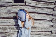 Muchacha adolescente alegre en ropa casual y el sombrero azul que presentan por una pared de madera Forma de vida activa Moda de  Imagenes de archivo
