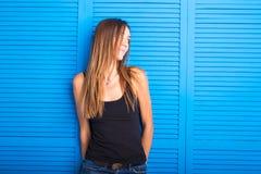 Muchacha adolescente alegre hermosa en top del negro sobre fondo azul Imagen de archivo libre de regalías