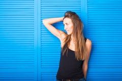 Muchacha adolescente alegre hermosa en top del negro sobre fondo azul Fotos de archivo