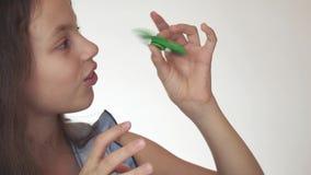 Muchacha adolescente alegre hermosa que juega con el hilandero verde de la persona agitada en el vídeo blanco de la cantidad de l metrajes