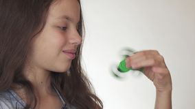 Muchacha adolescente alegre hermosa que juega con el hilandero verde de la persona agitada en el vídeo blanco de la cantidad de l almacen de video