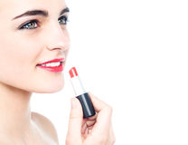 Muchacha adolescente alegre que aplica el lápiz labial rojo Imágenes de archivo libres de regalías