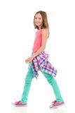 Muchacha adolescente alegre que camina, vista lateral Foto de archivo libre de regalías