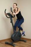 Muchacha adolescente alegre que completa un ciclo en la bici casera Fotos de archivo libres de regalías