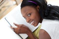 Muchacha adolescente alegre que estudia la mentira en un sofá Foto de archivo libre de regalías