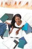 Muchacha adolescente alegre que estudia sentarse en su cama Fotos de archivo libres de regalías