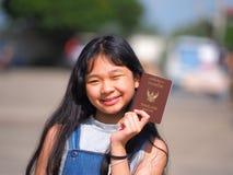Muchacha adolescente asiática con el pelo negro largo que sostiene el pasaporte tailandés Fotografía de archivo