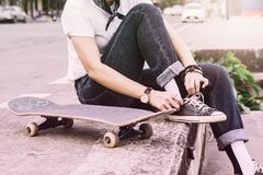 Muchacha adolescente asiática con estilo del monopatín en str del parque del patín del aire libre Imagenes de archivo