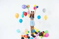 Muchacha adolescente asombrosa que mira derecho, llevando a cabo impulsos del helio en blanco Imagen de archivo