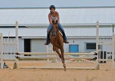 Muchacha adolescente atlética que salta un caballo sobre los carriles. Imagen de archivo