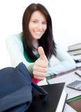 Muchacha adolescente atractiva con el pulgar para arriba que estudia Fotos de archivo libres de regalías