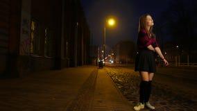 Muchacha adolescente atractiva en el baile de la falda y la diversión el tener en una calle de la noche almacen de video