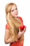 Muchacha adolescente atractiva en la camiseta anaranjada que sostiene una manzana roja Fotos de archivo libres de regalías