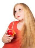 Muchacha adolescente atractiva en la camiseta anaranjada que sostiene una manzana roja Imagenes de archivo