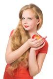 Muchacha adolescente atractiva en la camiseta anaranjada que sostiene una manzana roja Imagen de archivo libre de regalías