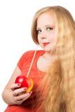 Muchacha adolescente atractiva en la camiseta anaranjada que sostiene una manzana roja Fotografía de archivo libre de regalías