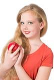 Muchacha adolescente atractiva en la camiseta anaranjada que sostiene una manzana roja Fotos de archivo