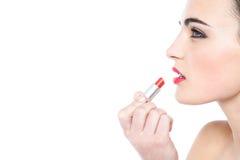 Muchacha adolescente atractiva que aplica el lápiz labial rojo Foto de archivo