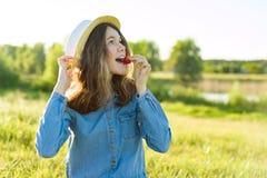 Muchacha adolescente atractiva que come la fresa Fondo de la naturaleza, paisaje rural, prado verde, estilo rural Imagen de archivo libre de regalías