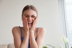 Muchacha adolescente avergonzada que ríe llevando a cabo las manos en las mejillas, headshot Foto de archivo