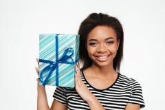 Muchacha adolescente bastante africana feliz que sostiene la actual caja Imagen de archivo