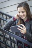 Muchacha adolescente bastante joven que mira el teléfono elegante Imagenes de archivo