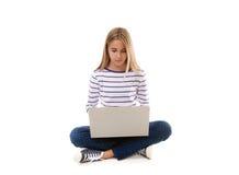 Muchacha adolescente bastante joven que se sienta en el piso con las piernas cruzadas y que usa el ordenador portátil, Fotografía de archivo