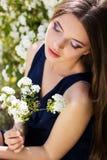 Muchacha adolescente bastante sonriente con ourdoors de las flores blancas Foto de archivo libre de regalías