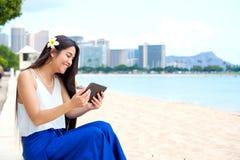 Muchacha adolescente Biracial en la playa usando la tableta, Waikiki, Hono Fotos de archivo libres de regalías