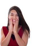 Muchacha adolescente biracial hermosa en el vestido rojo emocionado, manos en cara Imágenes de archivo libres de regalías