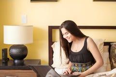 Muchacha adolescente biracial hermosa en la cama que mira el ordenador portátil Fotos de archivo libres de regalías