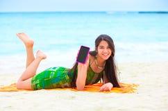 Muchacha adolescente biracial hermosa que miente en la playa tropical con el teléfono Imagenes de archivo