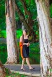 Muchacha adolescente biracial hermosa que miente en la playa tropical con el teléfono Imagen de archivo