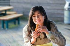 Muchacha adolescente biracial joven que come la hamburguesa Foto de archivo