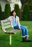 Muchacha adolescente biracial joven que se relaja al aire libre en banco de parque Foto de archivo libre de regalías