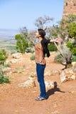 Muchacha adolescente Biracial que aumenta los brazos en alabanza en Grand Canyon Imágenes de archivo libres de regalías