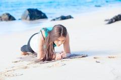 Muchacha adolescente Biracial que ejercita en la playa tropical, tablaje Imagenes de archivo