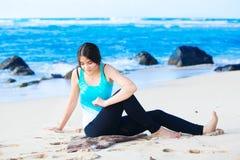 Muchacha adolescente Biracial que estira y que ejercita en la playa Imagenes de archivo