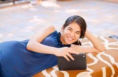 Muchacha adolescente Biracial que miente en banco al aire libre usando la tableta Imagenes de archivo