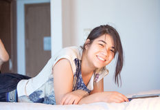 Muchacha adolescente Biracial que miente en la cama que sonríe, usando la tableta Fotos de archivo libres de regalías