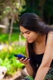 Muchacha adolescente Biracial que mira el teléfono móvil en el ajuste tropical Imágenes de archivo libres de regalías