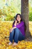 Muchacha adolescente Biracial que se inclina contra el árbol, hojas de otoño en groun Imagenes de archivo