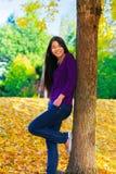 Muchacha adolescente Biracial que se inclina contra el árbol, hojas de otoño en groun Imagen de archivo
